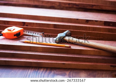 Interior wood working. FIne quality hardwood lumber, ready for use. pencil, measure, and a hammer on lumber. - stock photo
