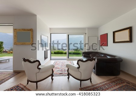 Interiors of new apartment, wide living room with white armchairs and many paintings on the wall - stock photo