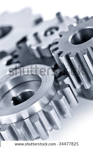 Interlocking industrial metal gears isolated on white - stock photo