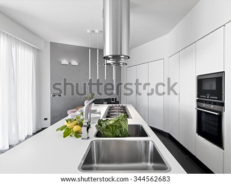 internal view of a modern kitchen in foreground still sink with vegetable and lemons on the worktop - stock photo
