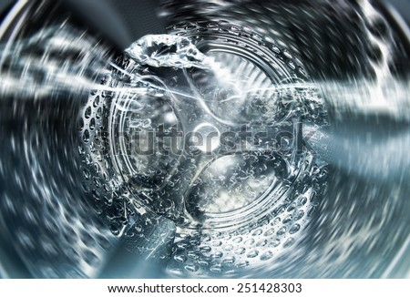 Internal view of an empty washing machine drum during wash - stock photo