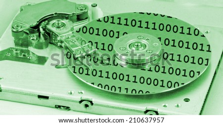 Internals of a computer harddrive with binary number reflections with green colors (HDD, winchester) - stock photo