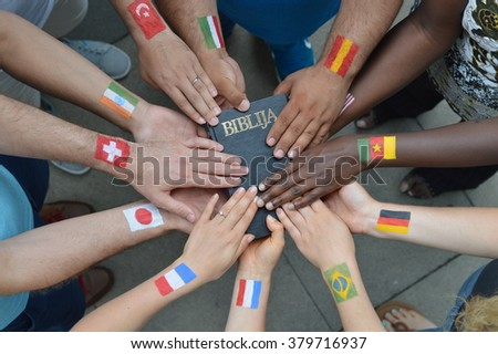 International brothers and sisters in Christ with different flags painted on their arms holding a bible together. - stock photo