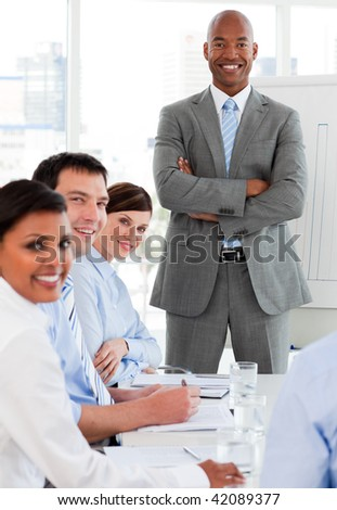International business team smiling at the camera in a meeting - stock photo