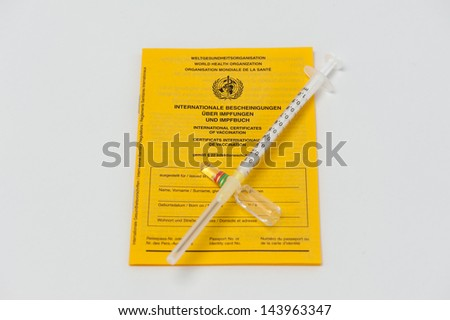 International Certificate of Vaccination with a Syringe and a Ampule isolated on white - stock photo
