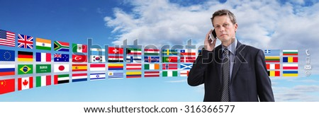 international contact, business man talking on the phone with flags on background - stock photo