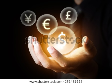 International currencies (US Dollar, Euro, Pound sterling, Japanese Yen) on businessman's hand - stock photo