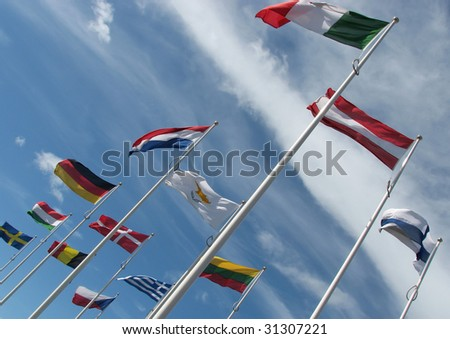 International flags flutter in blue cloudy sky - stock photo