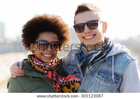 international friendship, relations, tourism, travel and people concept - happy teenage friends or couple in sunglasses hugging outdoors - stock photo