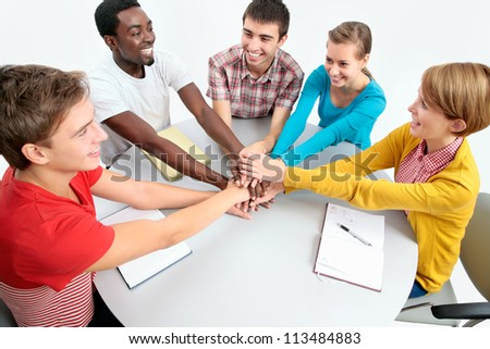 International group of students showing unity with their hands together - stock photo