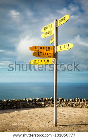 International signpost featuring various world capitals and their distances from Cape Reinga in the far north of New Zealand. - stock photo