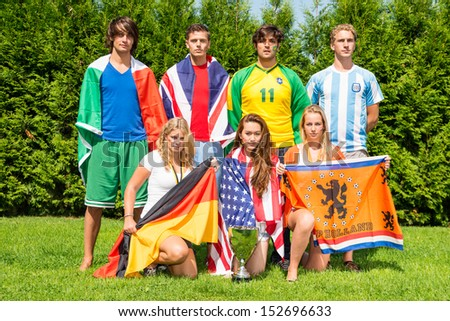 International sports team with men and women from various nationalities, each dressed in the color of their nation, holding their county's flags - stock photo