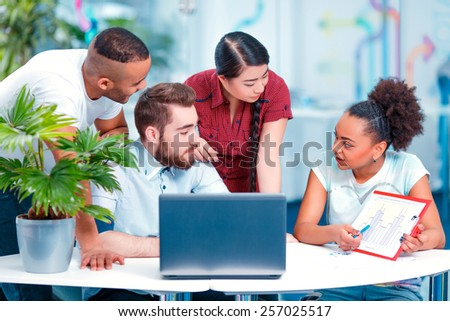 International students. Group of multinational young people in casual clothing discussing analytics during group classes in college - stock photo