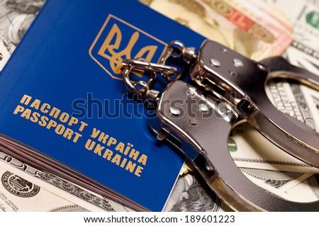 International Ukrainian passport with handcuffs on money background - stock photo