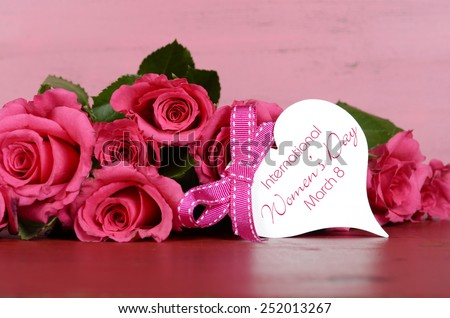 International Womens Day, March 8, pink roses with gift tag message on vintage pink wood background. - stock photo
