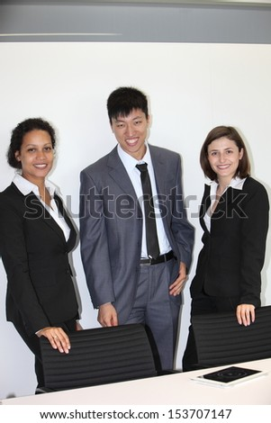 International young professional team made of one confident Asian businessman and two businesswomen smiling, wearing formal clothes while standing in the office - stock photo