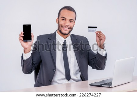Internet banking for business. Successful African businessman sitting at a laptop and holding credit card in hand until businessman doing orders through the Internet - stock photo