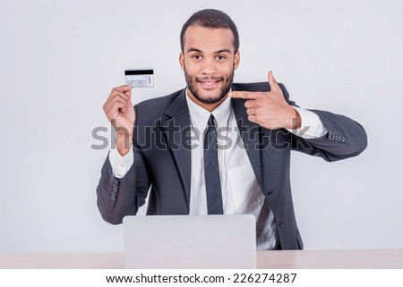 Internet banking. Successful African businessman sitting at a laptop and holding credit card in hand until businessman doing orders through the Internet - stock photo