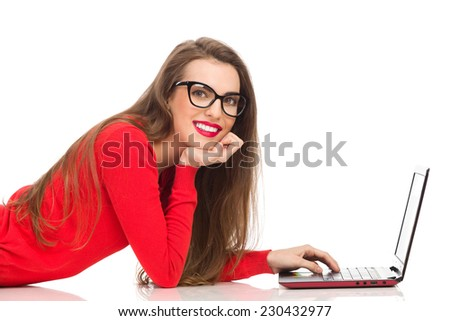 Internet flirt. Smiling beautiful girl lying down on a floor, using laptop and looking at camera. Full length studio shot isolated on white. - stock photo