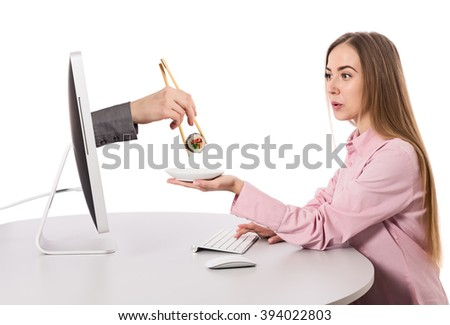 Internet Food ordering and instant Delivery young Woman makes Order at Computer Hand of Agent appears from Screen instantly delivering Order holding Sushi Roll wooden Chopsticks on white Background - stock photo