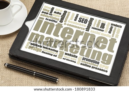 internet marketing - word cloud on a digital tablet with a cup of coffee - stock photo
