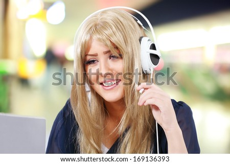 Internet telephony, happy girl on computer headset in public venue - stock photo