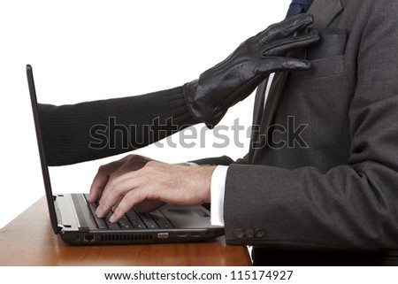 Internet theft - a gloved hand reaching out through a laptop screen to steal a wallet. - stock photo