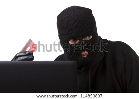 Internet Theft - a man wearing a balaclava sat behind a laptop holding a credit card, white background. - stock photo