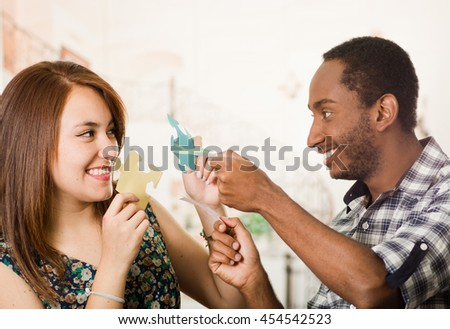 Interracial charming couple holding up large puzzle pieces and happily interacting having fun, blurry studio background - stock photo