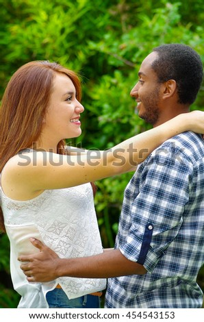 Interracial charming couple wearing casual clothes embracing and posing for camera in outdoors environment - stock photo