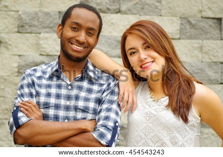 Interracial charming couple wearing casual clothes posing for camera and embracing in front of grey brick wall - stock photo