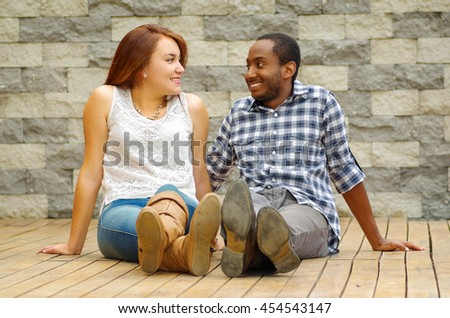 Interracial charming couple wearing casual clothes sitting on wooden surface posing for camera staring at each other, grey brick wall background - stock photo