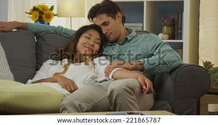 Interracial couple cuddling on couch - stock photo