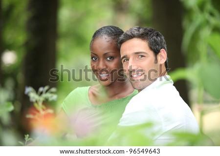Interracial couple in a park. - stock photo
