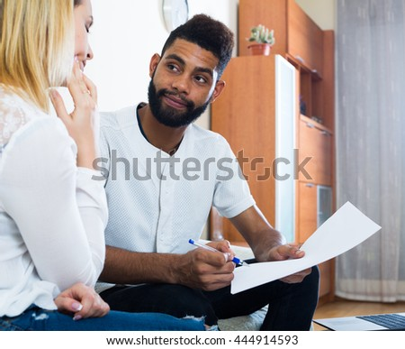 Interracial family couple filling papers for mortgage indoors - stock photo