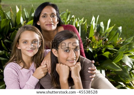 Interracial family - Indian mother with mixed-race daughters - stock photo