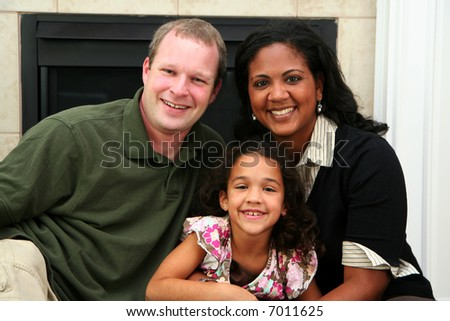Interracial family sitting together at home - stock photo
