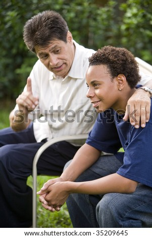 Interracial father and teenage son together in back yard - stock photo