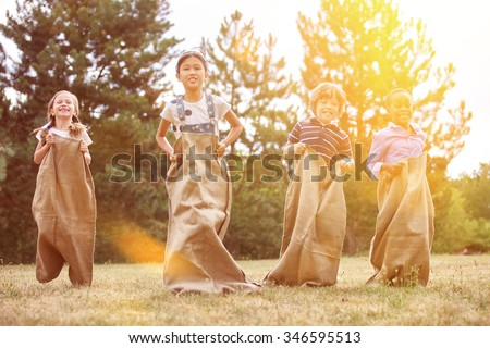 Interracial group of children competing in a sack race at the park - stock photo