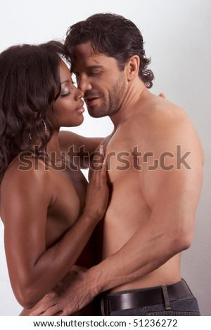 interracial heterosexual couple in sensual kiss. Mid adult Caucasian men in late 30s and young mulatto biracial female mix of black African American, Native American and German ethnicity in 20s - stock photo