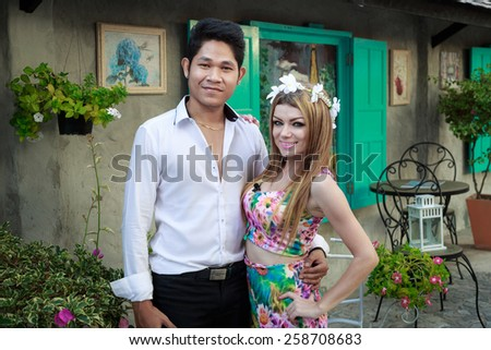 Interracial Love Couple Handsome Asian Man And Pretty Caucasian Woman Hugging And Posing In The Garden - stock photo