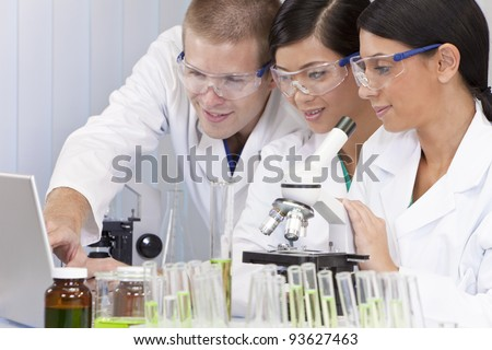 Interracial team of male and female medical or scientific researchers or doctors using a laptop & microscope in a laboratory. - stock photo
