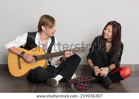 Interracial young couple music. Asian woman and Caucasian man. - stock photo