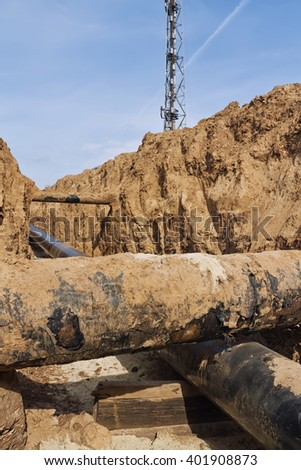 intersection of the projected pipeline with already existing inside the trench dug - stock photo