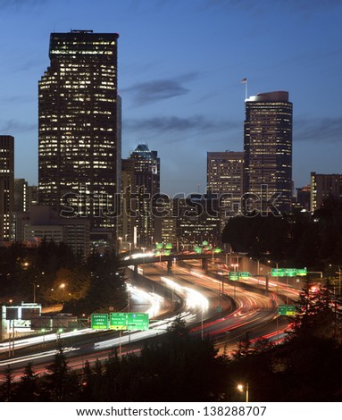 Interstate 5 cuts through Downtown Seattle as the sun sets - stock photo