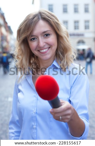 Interview of a young woman with blond hair in the city - stock photo