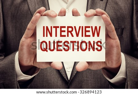 Interview Questions. Businessman holding a card with a message text written on it - stock photo