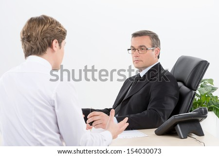 Interview. Two men in formalwear talking while sitting at the table - stock photo