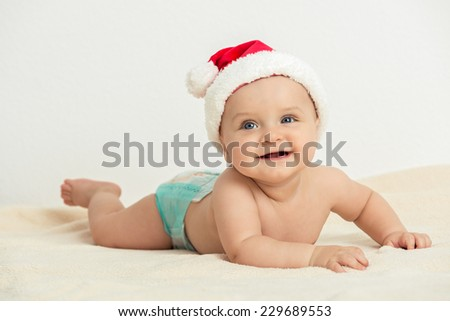 Intimate Christmas Feeling - Cute little baby boy lie prone and wearing Santa Claus hat - stock photo