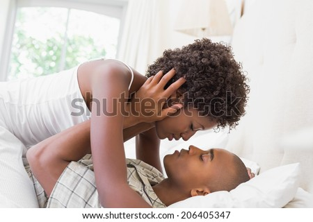 Intimate couple cuddling lying on their bed at home in the bedroom - stock photo